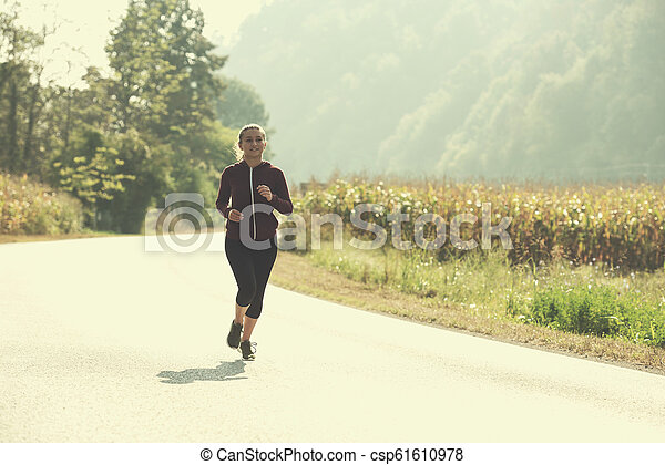 woman jogging along a country road - csp61610978