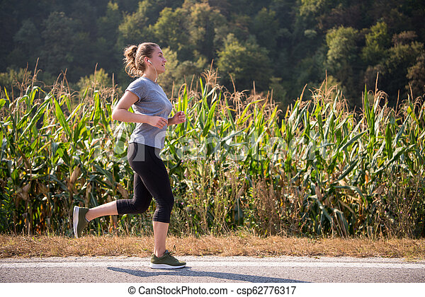 woman jogging along a country road - csp62776317