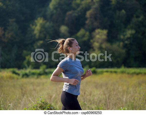 woman jogging along a country road - csp60969250