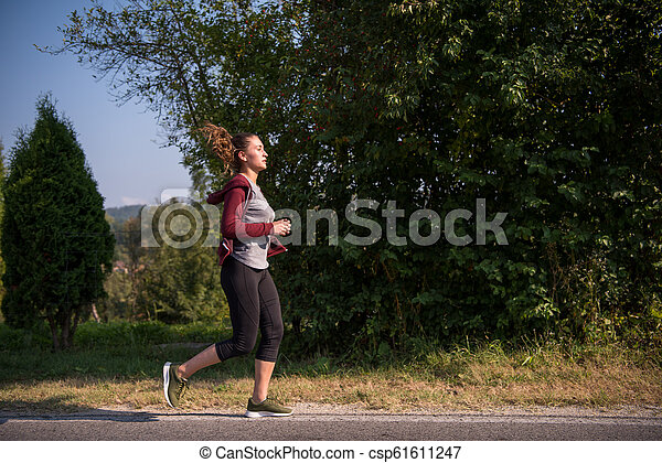woman jogging along a country road - csp61611247