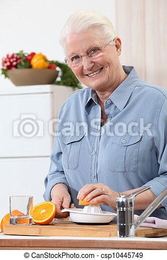 Woman juicing an orange - csp10445749