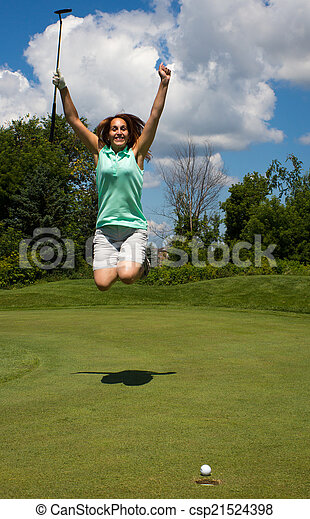 Woman jumping for joy as the golf ball heads into the cup - csp21524398