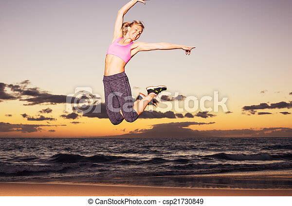 Woman jumping on the beach at sunset - csp21730849