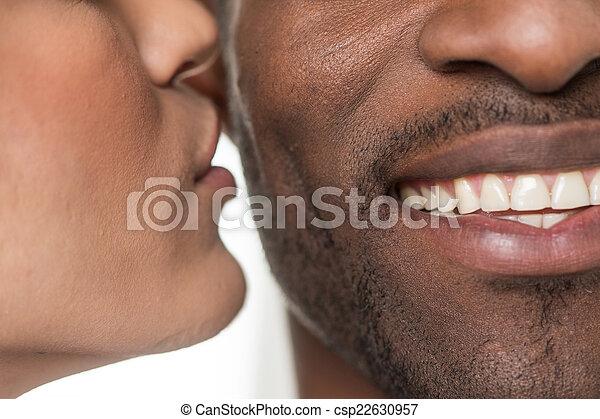 woman kissing black man on cheek. closeup portrait of african man smiling  - csp22630957