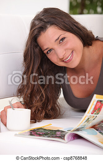 Woman laying on sofa with cup of coffee and magazine - csp8768848