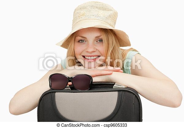 woman leaning on a suitcase while smiling - csp9605333