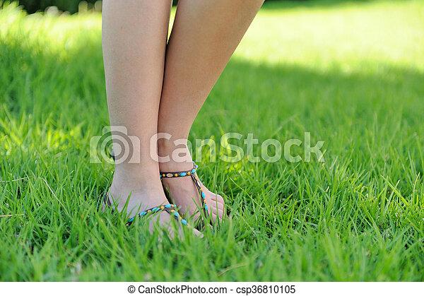 Woman legs walking on green grass - csp36810105