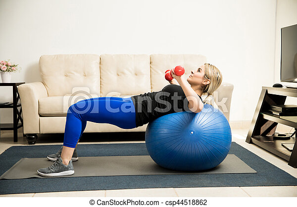 Woman lifting weights and using stability ball - csp44518862
