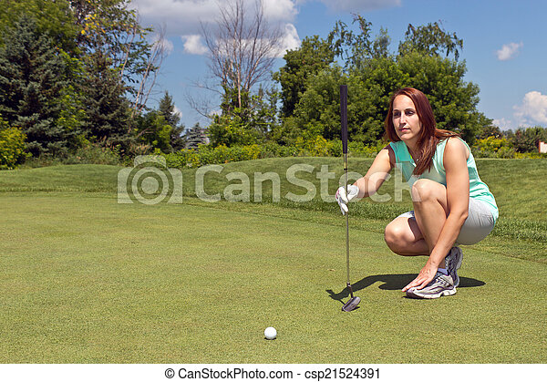 Woman lining up her putt on the golf green - csp21524391