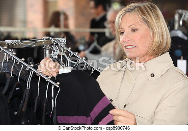 Woman looking at clothes in a shop - csp8900746