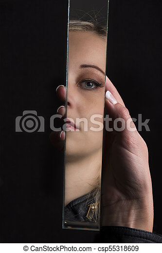 Woman looking at her face in shard of broken mirror - csp55318609