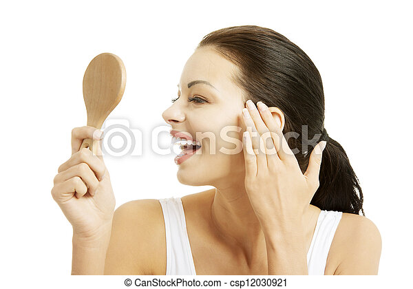 Woman looking at herself in the mirror - csp12030921
