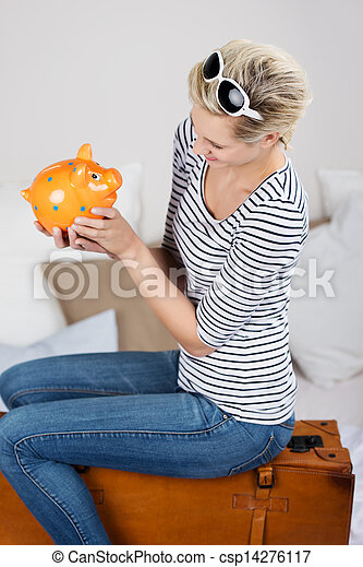 Woman Looking At Piggybank While Sitting On Suitcase In Bed - csp14276117