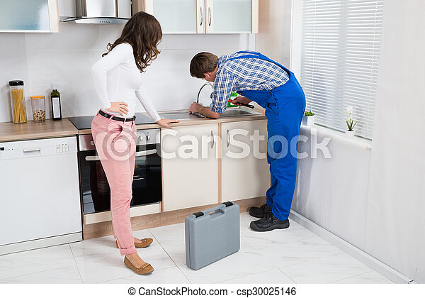 Woman looking at plumber fixing sink. Young woman looking at ...