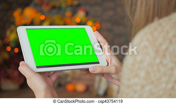 Woman looking at tablet computer with green screen - csp43754119