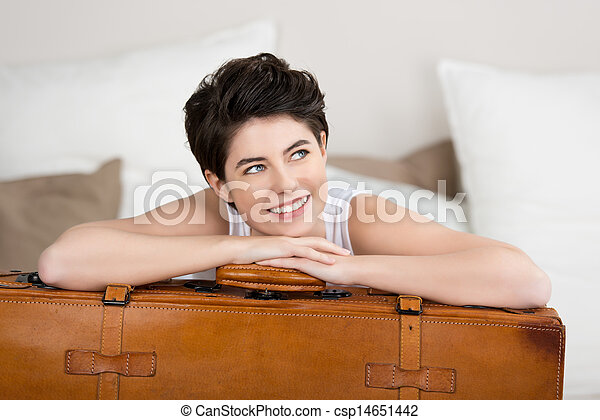 Woman Looking Away While Leaning On Suitcase - csp14651442