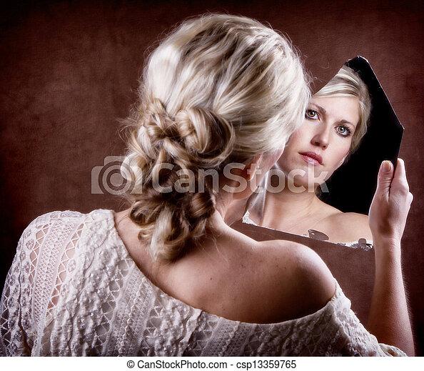 woman looking into a broken mirror - csp13359765