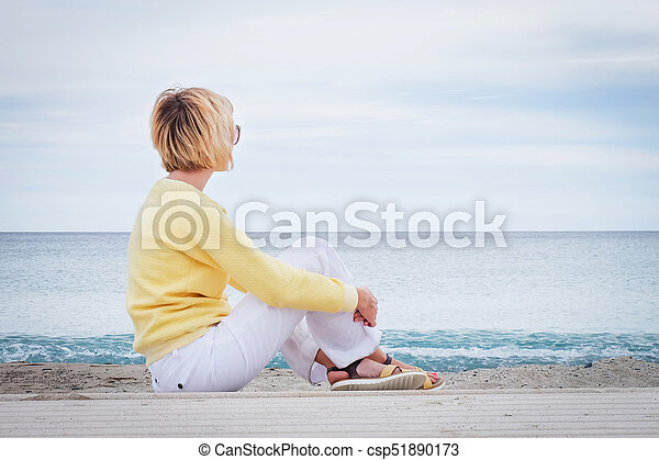Woman looking through the sea while sitting on beach - csp51890173