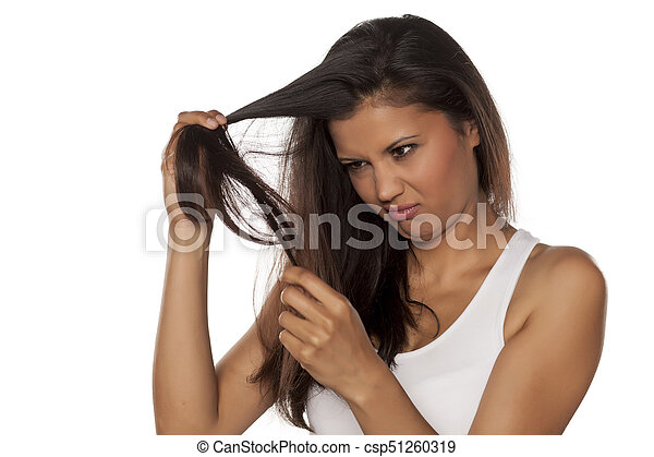 woman looks at her damaged hair - csp51260319