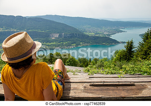 woman looks at Lake Annecy in summer - csp77462839