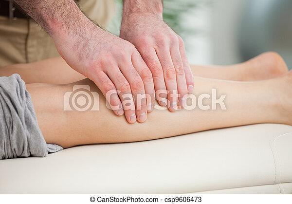 Woman lying forward while a man massaging her calf - csp9606473