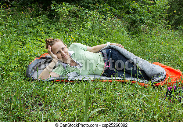 Woman lying in a sleeping bag in a forest glade.