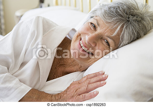 Woman lying in bed smiling - csp1892263