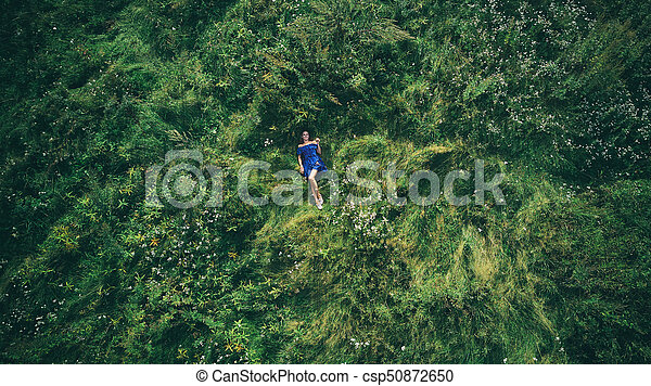 woman lying in the green grass. Top view - csp50872650