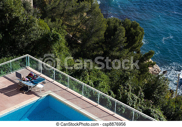 Woman Lying Next To A Pool In The Sun - csp8876956