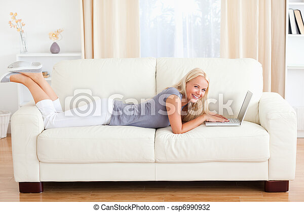 Woman lying on a sofa with a notebook - csp6990932