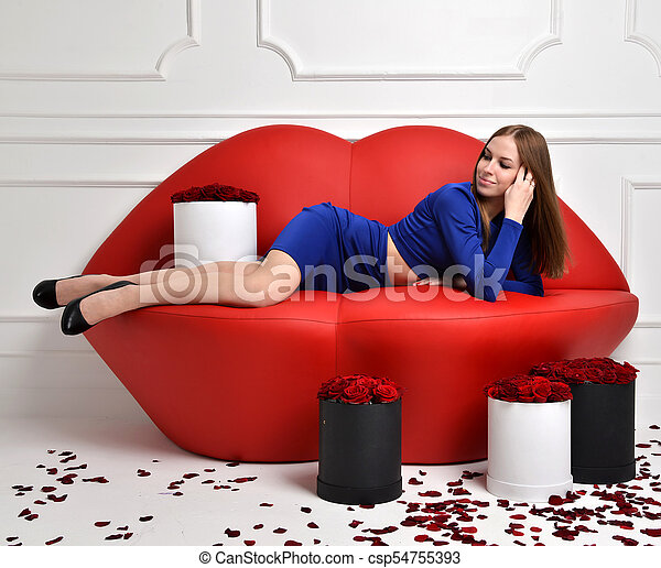 Woman Lying On Red Lips Sofa Couch In Blue Dress Smiling With Roses Bouquet  Flowers Petals