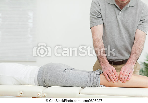 Woman lying while a man is massaging her calves - csp9605927