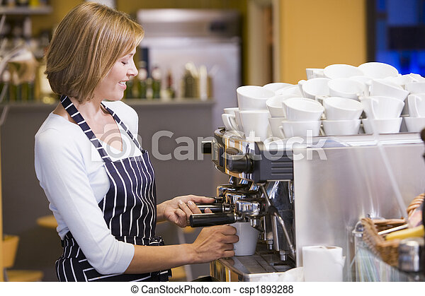 Woman making coffee in restaurant smiling - csp1893288