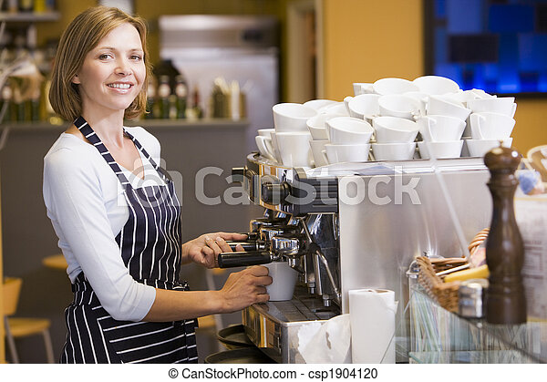 Woman making coffee in restaurant smiling - csp1904120