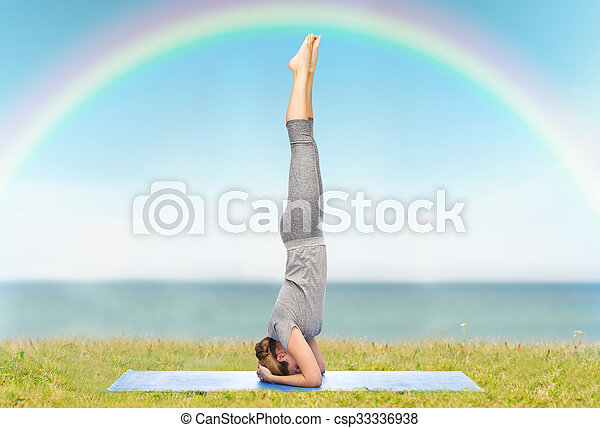 woman making yoga in headstand pose on mat stock photo