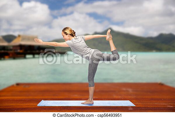 woman making yoga lord of the dance pose outdoors fitness