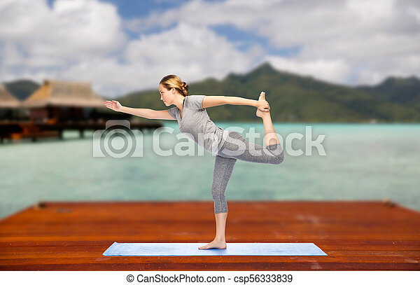 woman making yoga lord of the dance pose outdoor fitness