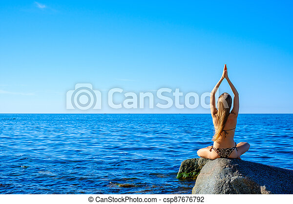 Woman meditating at morning near sea - csp87676792