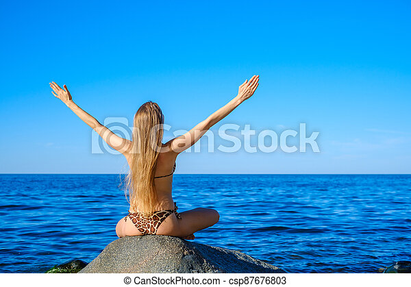 Woman meditating at morning near sea - csp87676803