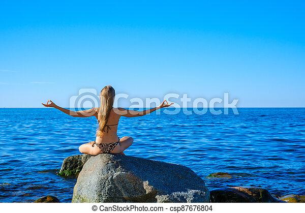 Woman meditating at morning near sea - csp87676804