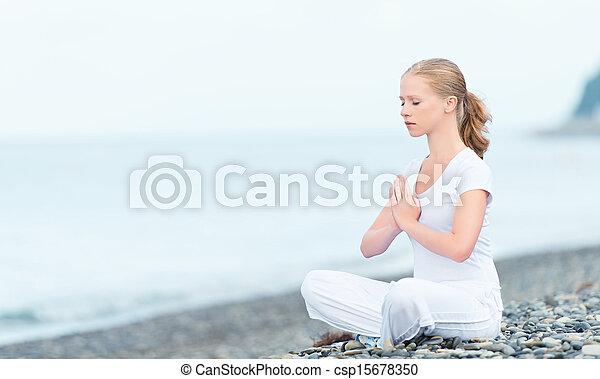 woman meditating in  lotus yoga on beach - csp15678350
