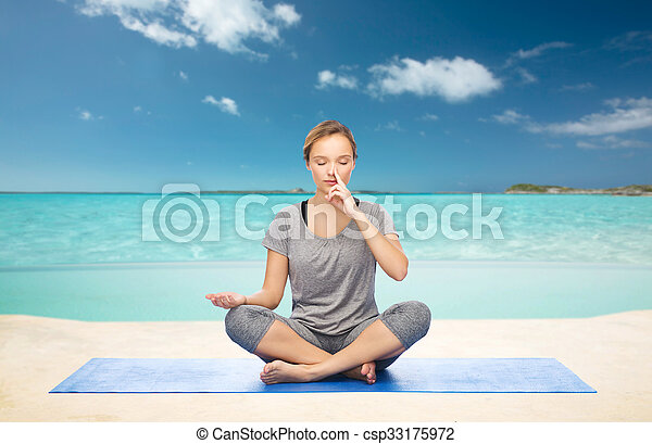 woman meditating in lotus yoga pose on beach fitness