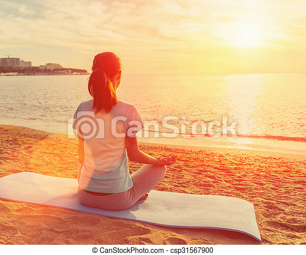 woman meditating in pose of lotus at sunset young woman