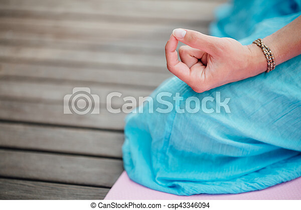 woman meditating in the lotus position closeup hands