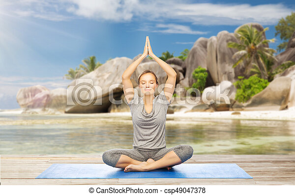 woman meditating in yoga lotus pose on beach fitness