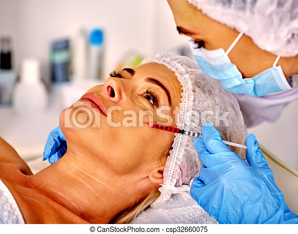 Woman middle-aged in spa salon with beautician. Female giving botox injections. - csp32660075