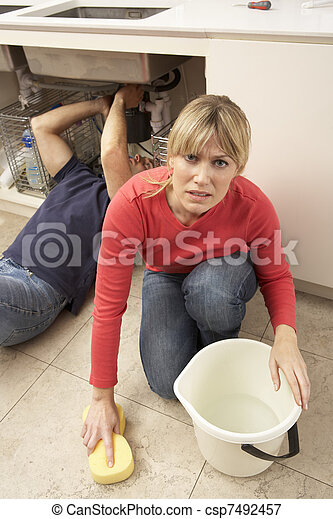 Woman Mopping Up Leaking Sink Whilst Plumber Works - csp7492457