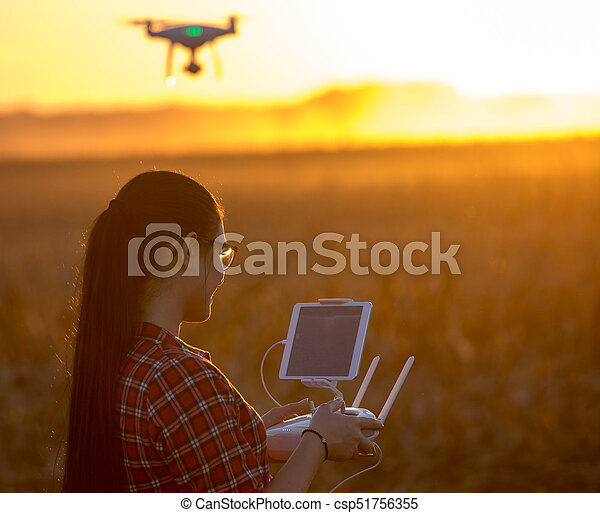Woman navigating drone above farmland - csp51756355
