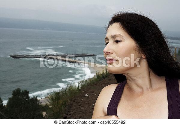 Woman near the sea in a public park - csp40555492