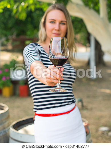 Woman offering glass of red wine at the winery. - csp31482777
